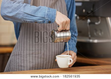 Coseup of barista at bar counter preparing cup of latte for customer in coffee house.