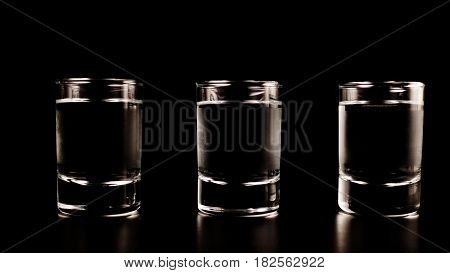 Three glasses, a shot of frozen vodka on a black table, on a black background