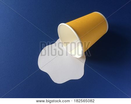Milk spilled from yellow disposable cup on blue background. Paper craft concept.