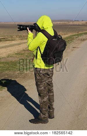 Wildlife photographer with long lens in the nature