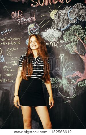 young cute teenage girl in classroom at blackboard happy smiling, education people concept close up