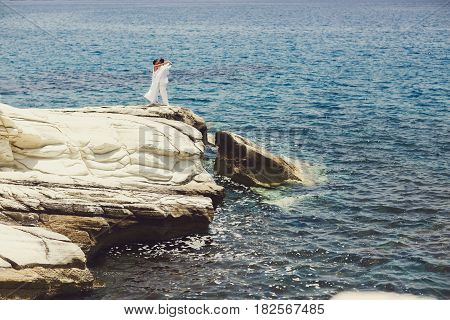 Just Married Couple In White Clothes Kisses On The Stone Sea Shore