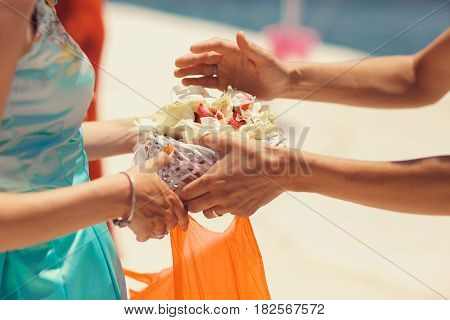 Man takes a palte with petals from woman's hands