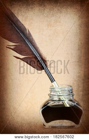Quill pen in ink bottle on brown background Vintage style image