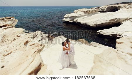 Bride Leans To A Groom Kissing Him On The White Stone Sea Shore