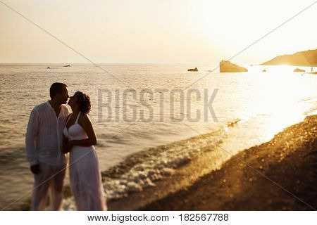 Bride Leans To A Groom Standing On The Bright Sea Shore While Sun Sets Behind Them