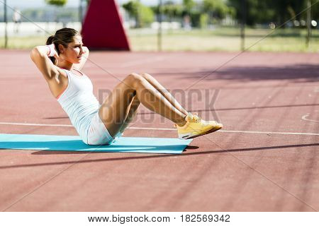 Young beautiful woman exercising outdoors by doing situps