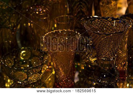 A gold glass vase on a background of blurred vases. Good for a background