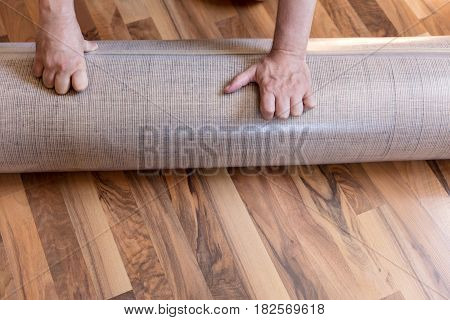 man´s hand with a new rolled carpet on the floor plastic packaging