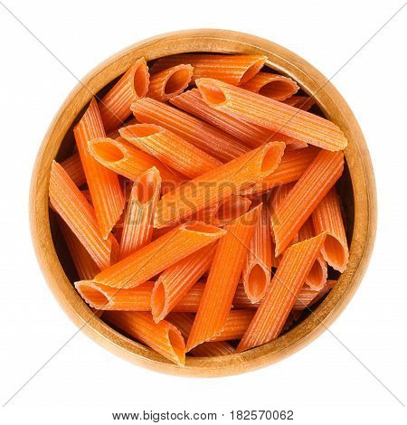 Red lentils penne pasta in wooden bowl. Uncooked dried glutenfree noodles. Lens culinaris. Short-cut medium length tubes with ridges cut diagonally at the ends. Macro food photo from above over white.