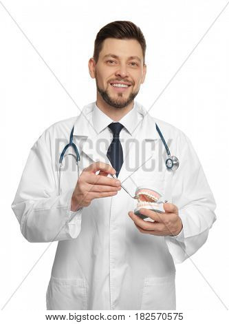 Handsome dentist standing on white background