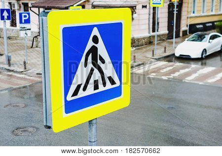 Road sign pedestrian crossing On the background of a road and a pedestrian crossing