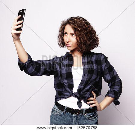 Pretty hipster girl taking selfie. Studio shot.