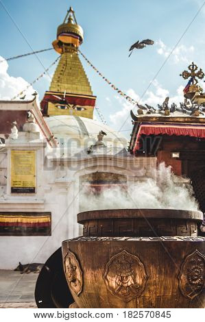 Atmospheric photo of Boudhanath stupa in Kathmandu Nepal. Incense smoke rises from a burning cauldron. It is the largest stupa in Nepal and the holiest Tibetan Buddhist temple outside Tibet.