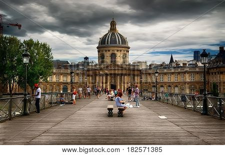 View on facade of Institut de France in Paris from Pont des Arts at cloudy day