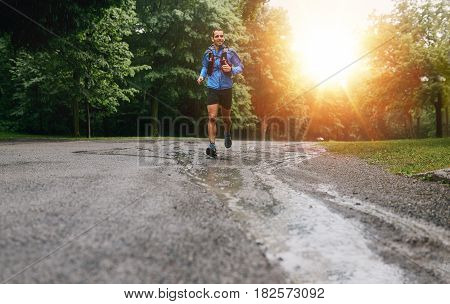 Leg detail of a competitive, athletic young man running off road outdoors at sunset through the woods in mud and water puddles on a trail in the afternoon wearing sportswear.