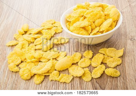 Corn Flakes In Glass Bowl And Scattered On Table