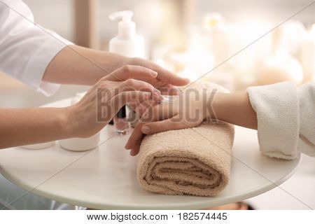 Young woman undergoing hand treatment in spa salon