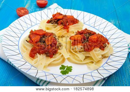 Pasta nest tagliatelle with bolognese sauce and vegetables on a plate.