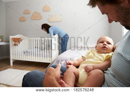Mother Making Up Bed In Nursery Cot For Newborn Son