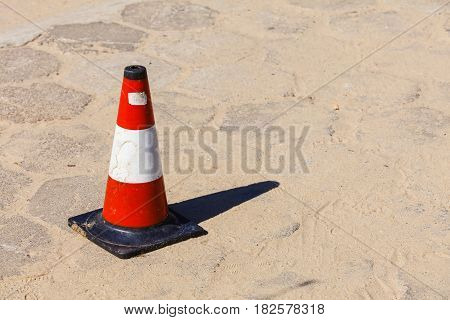 Stop warning white and red bollard cone on sandy beach. Attention during summertime