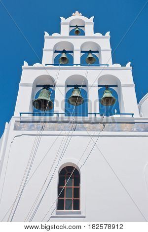 Big bell tower with 6 bells of Panagia church at Oia village at Santorini island, Greece