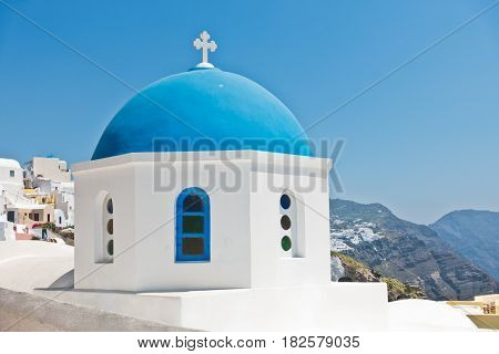 Blue dome of a white church with Caldera cliff in a background, Oia village, Santorini island, Greece