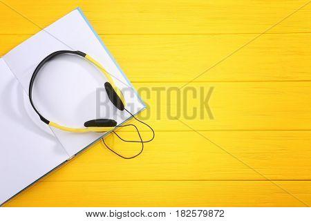 Audiobook concept. Open book with headphones on wooden background