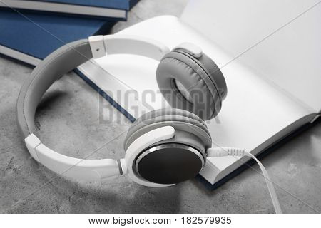 Audiobook concept. Open book and headphones on gray background