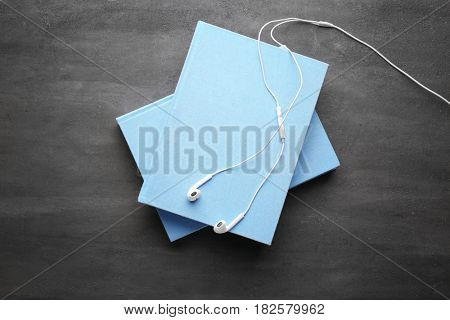 Audiobook concept. Stack of books and earphones on gray background