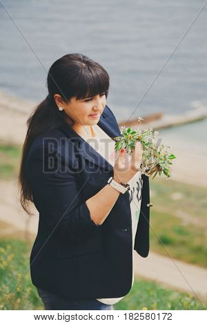 Happy Smiling Beautiful Overweight Young Woman In Dark Blue Jacket Outdoors Near To The Sea With Flo