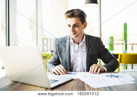 Businessman Working With Laptop And Documents In Modern Office