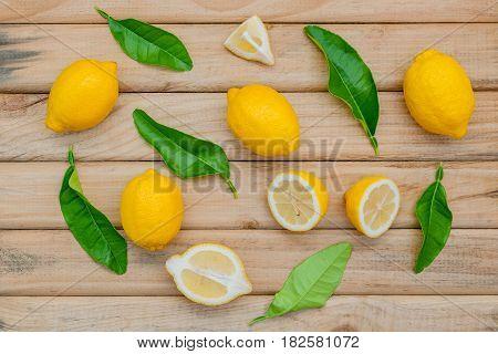 Fresh Lemon And Lemon Leaves On Rustic Wooden Background. Lemon And Lemon Slice On Wooden Table With