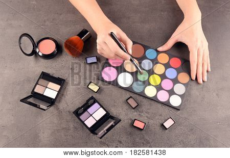 Female makeup artist with cosmetics at work