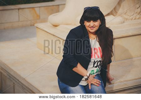 Happy Smiling Beautiful Overweight Young Woman In Dark Blue Jacket Sitting Outdoors. Confident Fat Y