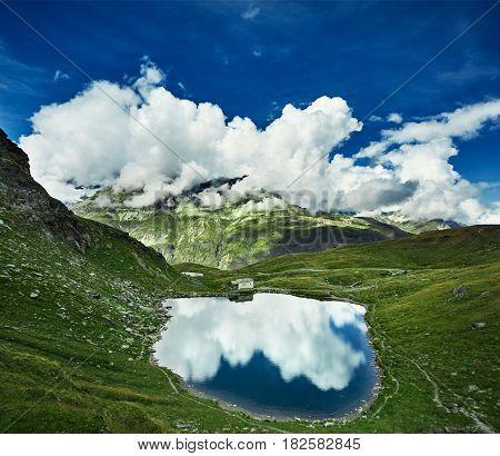 Idyllic summer landscape with clear mountain lake in the Alps. Trek near Matterhorn mount