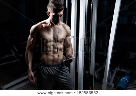 A young man bodybuilder with a naked torso listening to music on headphones in the gym