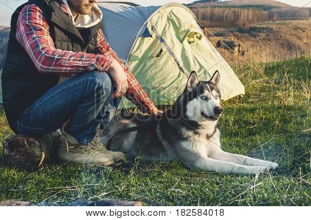 Close-up Guy bearded in jeans checkered shirt and a sleeveless jacket with a dog husky on vacation sitting on nature next to the tent in the evening at sunset.