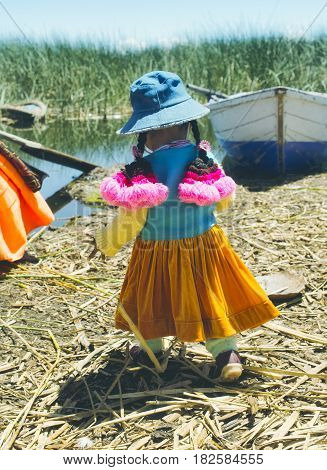 Aymara girl dressed in colorfull outfit The Uros Islands. October 16 2012 - Lake Titicaca Peru