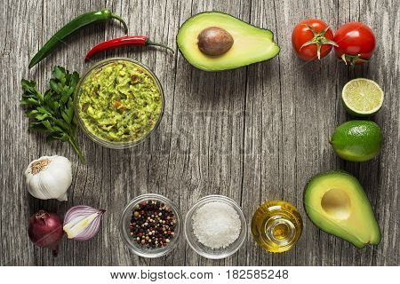 Avocado guacamole with fresh ingredients on wooden table