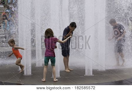 Montreal, Quebec - June 27, 2015 - Wide view of children playing in the automated water fountains at the International Jazz Festival in downtown Montreal Quebec on a bright day at the end of June.