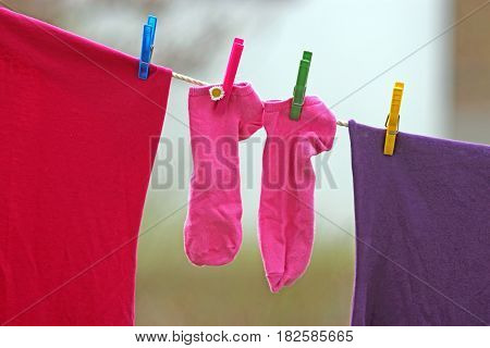 little pink childrens socks on the clothesline
