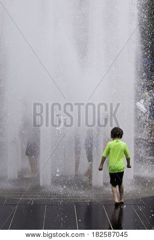 Montreal, Quebec - June 27, 2015 - Vertical of a little boy entering the automated water fountains at the International Jazz Festival in downtown Montreal Quebec on a bright day at the end of June.