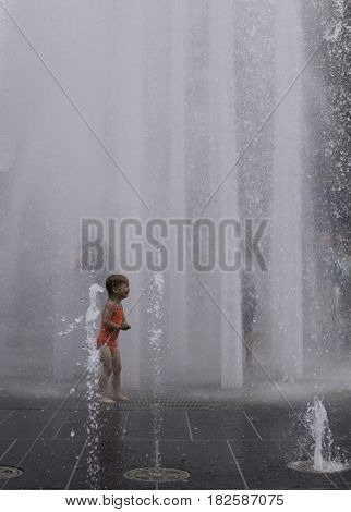 Montreal, Quebec - June 27, 2015 - Vertical of a little girl crying as the automated water fountains send up huge sprays at the International Jazz Festival in downtown Montreal, Quebec on a bright day at the end of June.