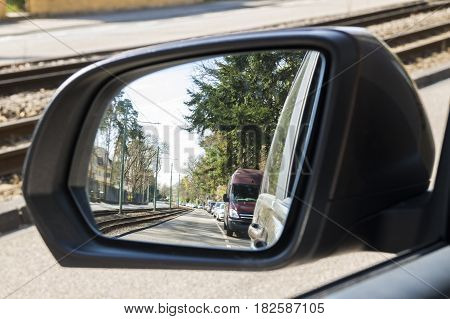 Side View Mirror In Modern Car With View Of Street With Parked Cars