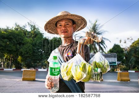 YANGON, MYANMAR - MARCH 3, 2017: Burmese poor man selling street fruits and water on Pyay Road in Yangon on March 3, 2017.