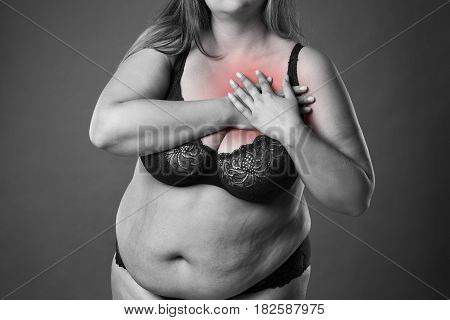 Fat woman with heart attack pain in chest overweight female body on gray background black and white photo with red spots