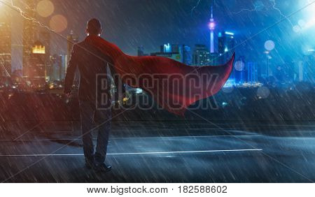 Businessman in a suit and cape hero facing a stormvictory concept. cityscape background night scene .