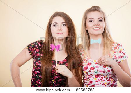 Two Happy Women Holding Carnival Accessoies On Stick