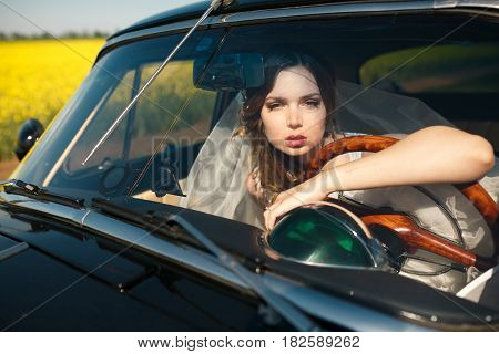 Stunning bride looks through the car's window leaning on a wheel